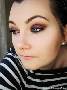 Apply brown base (here, Anastasia Dipbrow Pomade in Dark Brown) over entire lid, blending out and up. Pat MUG Burlesque onto lid for intense color, also blending out and up. Top with KOBO 502 Misty Rose (iridescent pink; substitute MAC Seedy Pearl?) to shift the color, and bring the iridescent pink into the inner corner. MUG Bada Bing to outer corner; gently drag onto outer lower lashline. Black gel liner on upper and lower waterline. Blend out the crease with MUG Peach Smoothie.