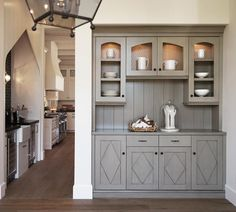 Gray butler's pantry is fitted with gray diamond pattern cabinet doors adorning oil rubbed pulls and a gray countertop fixed against a gray shiplap backsplash beneath custom lit upper cabinets accented with chicken wire doors.