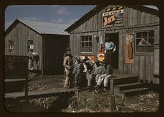 """Migratory laborers sit outside of a """"juke joint"""" at Belle Glade, Florida in February 1941. A man stands on left holds a gun. Photo taken by FSA photographer Marion P. Wolcott. Learn more about African American History and Photography, visit Digital Diaspora Family Reunion DDFR www.DDFR.tv. The whole collection can be found in the Library of Congress. www.loc.gov/pictures/collection/fsac/  Upload and share your own family photographs and stories at ddfrsocialnet.ning.com !"""