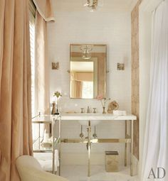 A guest bath features an étagère and mirror by Restoration Hardware and sconces from Circa Lighting; the washstand, sink fittings, and tiles are by Waterworks.