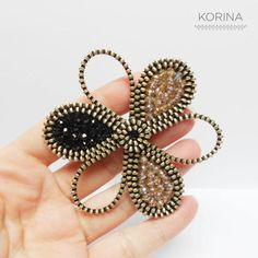 Flower zipper brooch This unique brooch is made of nickel zipper and glass beads which are all sewn by hand. The back of brooch is genuine leather. Its a perfect detail for your favorite sweater, coat or blazer. Measures about 3 in (7.5 cm) across. If you have any questions about