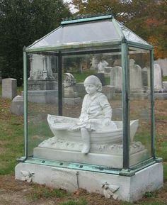 Boy in a Boat  Forest Hill Cemetery Jamaica Plain, Massachusetts (Boston)  Also erected with the monument was a marble bench with a moveable drawer (since removed), where the grieving mother could come to clean the glass, polish its brass fitting, place flowers, and do other duties as she saw fit.  Due to financial reverses, Mme. Mieusset's private income ceased, and she went to work as a domestic on Beacon Hill.