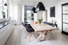"""""""Min bästa möbel är mitt matbord"""". Så gott som alla bord i huset är designade av Pia. Stolarna är designade av Eames. Taklampor från Kartell. På bordet står en vas från Ikeas serie Sinnerlig och en skål i olivträ som Pia och Henrik köpt på Gotland. På bänken mot väggen, två kuddar från Lovely Linen och på väggen ovanför hänger Pias tavla """"kvinna på språng"""". Lammfällarna är alla från Gotland."""