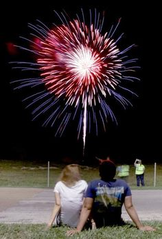Jessica Conner and J.J. Garza watch the fireworks show from a curb at the Victoria Mall. The couple recently moved to Victoria from Ben Bolt. Wednesday night was their first time seeing the Victoria fireworks together.