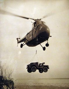 "330-PS-3293-1:   ""Mighty Mite,"" a revolutionary ¼-ton, light-weight truck that is capable of towing trailed loads, transporting weapons and radios and evacuating casualties, is being carried by helicopter using a special demonstration March 26, 1953, at the Marine Corps School, Quantico, Virginia.  High government, military, and industrial officials, who were present at the demonstration noted that ""Might Mite"" can perform tasks which heretofore have not been possible with present vehicle…"