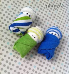 Diaper babies~diaper wrapped in baby washcloth topped with baby sock hats. Adorable baby shower idea!