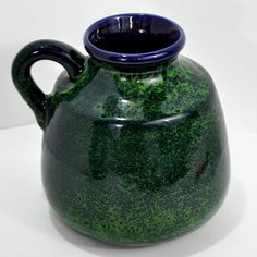 Gorgeous blue and green glaze handle vase or jug from Beauce Ware Pottery Quebec Canada. This piece is in perfect as new condition and was made between 1950-1970s. It is a wonderful piece of Canadian pottery and an unusual combination of colors from Beauce Ware. This piece is in perfect condition with no chips or marks to the glaze whatsoever. It is a classic piece of pottery and wonderful as a vase or decorative jug. It is stamped and marked on the bottom. DIMENSIONS: Approx. 5 1/2 inches…