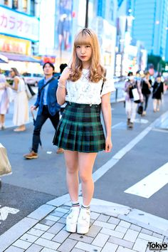 19-year-old Manameru on the street in Harajuku wearing a Morph8ne top, plaid skirt, and YRU platform sandals with striped socks.