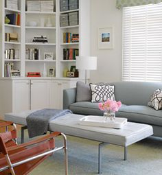 Our sofa and ottoman/chair are leather trimmed so there are good ideas here. A sleek brown leather chair is a great pop of color and texture in a monochromatic living room. We also love the polka dot window treatments!