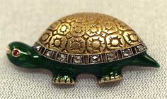 """This little turtle is full of character! He sports quite the elaborate shell, with detailed engraving and a border of genuine rose cut diamonds. His body is rich, green enamel and his eye a glittering, genuine ruby. Crafted from 14K yellow gold and fitted with a sturdy trombone clasp. The brooch measures 1 1/8"""" x ¾"""" and weighs 4.9 dwt (7.6 grams) ca. 1930"""