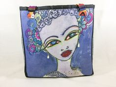 """Grace - Graceful Beauty This bag measures 15"""" wide by 16"""" high by 6"""" deep The image is painted and dyed on linen Grace is wearing faux pearl drop earrings The back and sides are a gray tweed-like fabric The inside has a nice blue floral print with a 5"""" x 7"""" open side pocket All seams are tailored with pretty black ribbon 9"""" multi-colored woven straps"""
