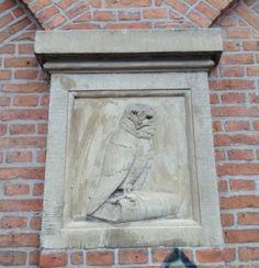Stone owl sitting on book.