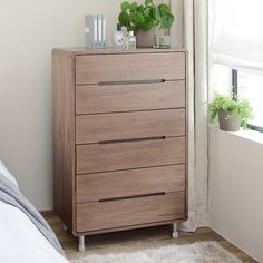 The minimalistic notch handles combined with curved edges in a grained walnut veneer and tubular legs make this six-drawer chest a contemporary feature in the bedroom. Beds, bedside tables and wardrobes are also available in the Notch range to complete the look.