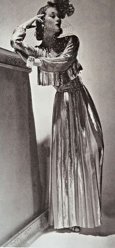 Lud in a fluid pleated lamé evening ensemble by Chanel, ivory cuff bracelet by Verdura, photo by Horst P. Horst, 1937