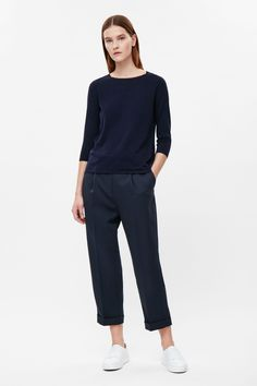 This top is made from fine knit cotton with a contrast silk back panel. Buttoning up along the back, it has a round neckline, 3/4 sleeves and neat ribbed cuffs.