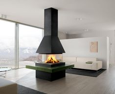 LUND SURROUND: Stylishly original fireplace with very large majolica elements for the base that can be made in your favourite colour chosen from among those in the Piazzetta palette. Frame, support, trim and hood in steel with black or white enamel finish. Fireplace fitted with an exclusive electrically-operated rise and fall system for the all-round glass screen. (the photo shows the Oliva majolica version, wood-burning firebox M360 Q).  www.calore.co.za