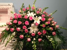 Fresh casket spray using white lilies, white snapdragons, pink roses and pink wax flower as filler. January 2016