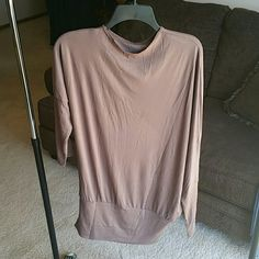 SEXY COCOA TUNIC TOP /DRESS Trendy and Very in Style Round neck can be worn as top or mini dress. LIightweight but not cheap cotton/poly blend. One sleeve is draped or dolman but slim and fitted over forearm.  Other sleeve is elbow length & fitted. Looks beautiful on...I have one for myself. This is New in bag. No tags as I bought from vendor. Boutique Tops Tunics