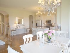 Huge country kitchen with Nordic French shabby chic style/white oak flooring/white painted dining table and Swedish style chairs/antiqued silver chandelier/staircase in kitchen/quartz countertops/archways/Hello Lovely Studio
