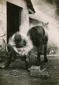 A farmer buring the hoof of a horse before shoeing it in Scotland, May 1921.  Photograph by William Reid, National Geographic