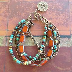 This multi-strand bracelet features 1 strand of orange rust Czech glass rectangle beads with a pretty blue Picasso finish, 2 strands of mixed