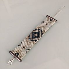 Très jolie Manchette faite au métier à tisser ,en perles de verre miyuki delicas 11/0 argent duracoat, Midnight aqua et opaque light mint. Ce bracelet mesure dans sa totalité 17, 5 cm sur 2,5 cm de largeur, la chaînette de rallonge mesure 5 cm. Tous les apprêts sont en argent. Livré