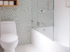 petite salle de bains avec baignoire et mosaique murale blanche