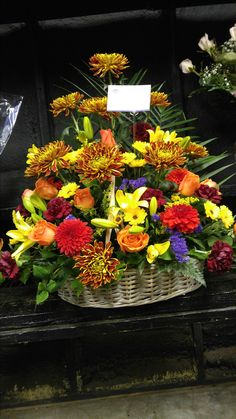 Beautiful handcrafted autumn colors in this funeral basket design. americasflorist.com