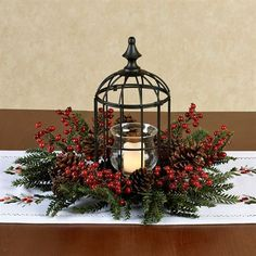 Give your holiday decor a soft, gentle glow and a display of an appealing floral medley with the Holly Berry Birdcage Candleholder. Metal birdcage has a small glass hurricane to hold your votive or tealight candle and is encircled by faux pine branches, red berries, and pine cones.