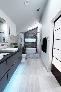 Brushed nickel shower head with digital shower valve, victoria and albert bathtub, curbless shower with hidden shower drain, flat pebble shower floor, shelf over tub with LED lighting, gray vanity with drawer fronts, white square ceramic sinks, wall mount faucets and lighting under vanity.