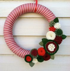 A fun handmade 12 wreath wrapped in red houndstooth ribbon. This wreath is decorated with a variety of greens, red, maroon, and cream felt flowers Felt Flower Wreaths, Felt Flowers, Yarn Wreaths, Fabric Wreath, Diy Wreath, Wreath Ideas, Holiday Wreaths, Holiday Crafts, Primitive Wreath