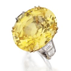 PLATINUM, 18 KARAT GOLD, YELLOW SAPPHIRE AND DIAMOND RING.    The oval sapphire weighing 36.21 carats, flanked by trapeze-cut and bullet-shaped diamonds weighing approximately 1.40 carat