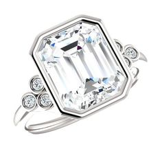A stunning colorless, emerald-cut, 10x8mm (4.00 ct) Supernova Moissanite is bezel set in this 14k white gold engagement ring adorned with 2mm round diamond side stones on a plain, high polished band. (If you would like to customize this design or any other ring, please emailus for a quote.)Details:Certified SupernovaMoissaniteShape: EmeraldWeight: 4.00 carat (10x8mm)Color: D-EClarity: VVSSide Diamonds* Round* Color:F-G* Clarity:VS1-VS2* Weight: 0.18 carats