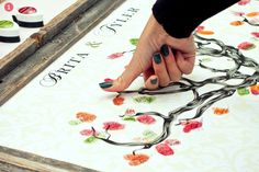 creative guestbook ideas: guests thumbprints on tree and write names on them