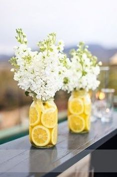Squeeze lemon juice in the water then use cranberries instead of lemons for appeal | Lemon jars and white flowers, baby's breath would work too, for an outside wedding. #OutdoorWeddings