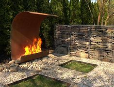 minimalist, dramatic but simple, combination of stone and metal, interesting shape, unusual way to view fire and protect yard. Would remove most of the stones, though.