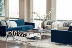 Blues take center stage in this classy living room, from the velvety sofas to the patterned pillows and even the coffee table books. Of course, there's no missing the zebra print sofa, which really livens up the soothing space. A flokati rug brings in a splash of whimsy, which is tempered by a clean-lined, contemporary coffee table. Flowering branches bring nature in and provide the crowning design touch to the space.