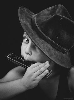 Use props - the hat is disproportionately sized to the child. Think: New Orleans or similar musician but presented in image of a child.