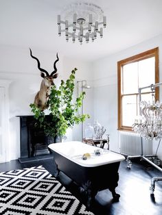 Black And White Bathroom with Dark Wood Flooring containing: Black And White Rug with Dark Clawfoot Tub also Wire Tub Caddy plus Dark Fireplace together with Decorative Deer Head with Modern Style Chandelier also Ceiling Molding