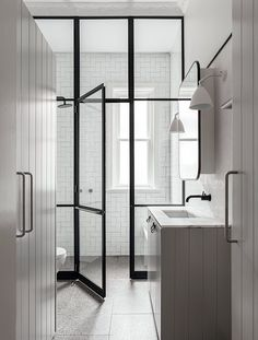 In/Out: Willoughby House by Arent&Pyke- Extending back into the house, the cabinetry becomes the wall and door of a concealed bathroom. Juxtaposing white geometric tiles with strong lines of black steel and impressive natural light, the bathroom is both grandly opulent and highly contemporary dominated by a floor to ceiling steel framed shower wall. On the floor, a mottled terrazzo tile of mixed greens, greys and brown creates a tonal midpoint between the otherwise monochromatic palette.