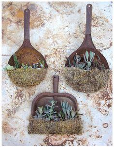 Old rusty dust pans as garden art....love it!