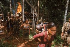 1964 US and South Vietnamese forces evict prostitutes from a suspected Vietcong village after setting it alight