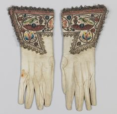ca 1620-1630 ladies gloves made of leather & silk, embroidered with silk and metal thread, spangles; embroidered with long-and-short, satin, knots, and couching stitches; plus metal bobbin lace. The cuffs are embroidered in similar naturalistic motifs seen in ladies jackets (or waistcoats). See detail pic for close up of embroidery.