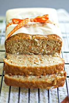 Carrot Coconut Bread with Cream Cheese Glaze - 1 1/4 cup shredded carrots  1 cup sweetened coconut flakes  1 1/4 cup flour  3/4 cup sugar  1 teaspoon baking powder  1 teaspoon salt  1/2 teaspoon baking soda  1 teaspoon cinnamon  1/4 teaspoon nutmeg  1/2 cup reduced-fat melted butter, cooled or vegetable oil  1/2 cup sour cream  2 eggs  1 teaspoon vanilla extract