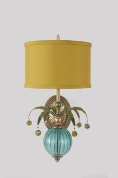 Wallflower 3 by Mollie Woods. Exuberant and colorful, this sconce features turquoise hand blown glass, green painted metal leaves with beads, hand painted polka dot accent, and green/gold fabric shade. Hardware is antique brass. Can be hard wired or wired with plug. 40 watt bulb included.