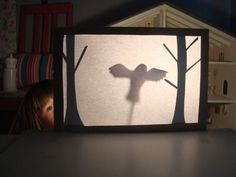 mousehouse: DIY shadow puppet theatre--out of a cereal box, trees as background, slit in box bottom for puppet 'sticks'