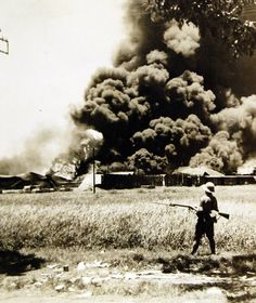 Lot 11630-2: Tanjong, Java, 1942. Burning oil tanks and oil cars left by the Dutch in retreating from Tanjong. Also: LC-USZ62-105186. Office of War Information Photograph.