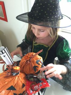 """My daughter is trying out her Halloween costume while putting the finishing touches on our ""You've Been BOO'd"" bucket (read: adding more candy!). Will she fly on her broom to deliver it? "" #BooitForward ="