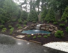 Re-landscaped area off driveway/garage in back of house - 900 tons of soil, large evergreens and another water feature.