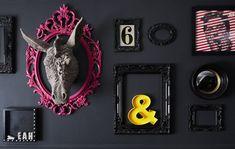 Eine schwarze Wand, dekoriert mit unterschiedlichen Rahmen und Gegenständen